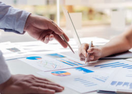 Business people or finance professionals analyze graphs, business reports and financial charts at corporate offices, economic concepts, finance, business, banking.